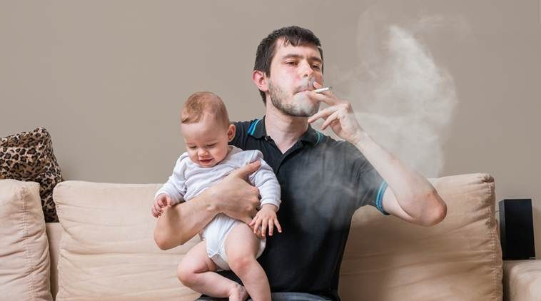 Bad father is smoking and holding baby.